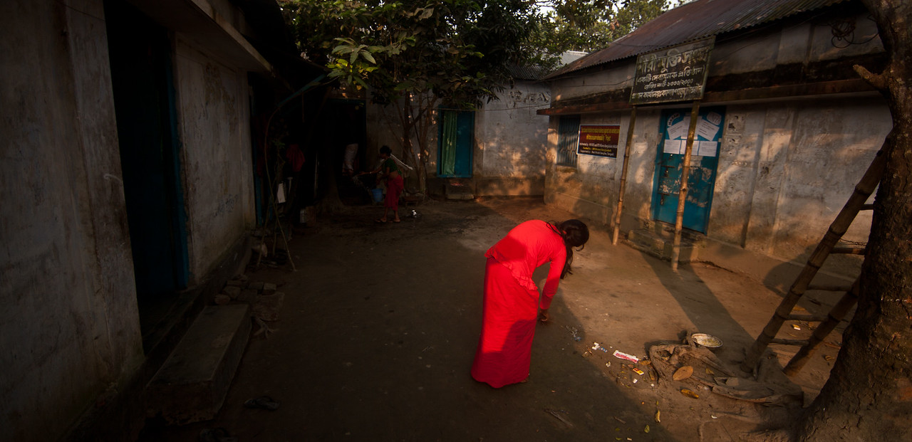It is early morning in a brothel area. After a working night, the sex worker sweeps the compound.