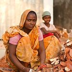 Women at work breaking bricks.